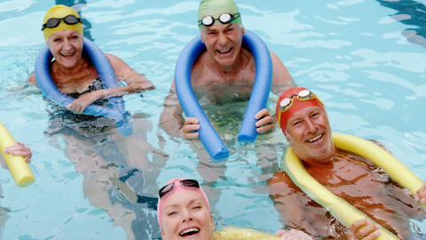 Portrait of senior citizens swimming with inflatable tube Footage