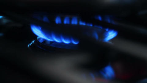 Close-up of blue flames under a burning oven stove top in kitchen cafeteria Footage