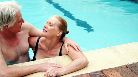 Senior couple embracing romancing in pool Footage