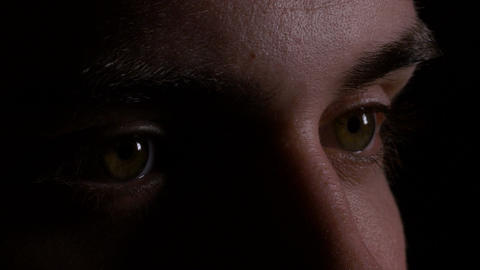 Close up macro of young man eyes looking and searching in the dark Footage