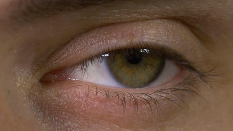 Closeup macro of young man eye blinking and looking around Footage