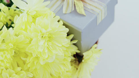 Gift box and bunch of yellow flowers in wicker basket with happy mothers day tag Live Action