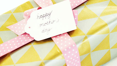 Gift box with happy mothers day tag on white background Live Action