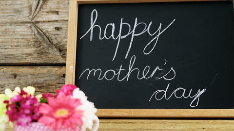Happy mothers day text written on chalk board with cup of flowers Live Action