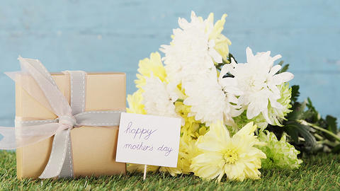 Gift box, happy mother day tag and flowers on grass Live Action