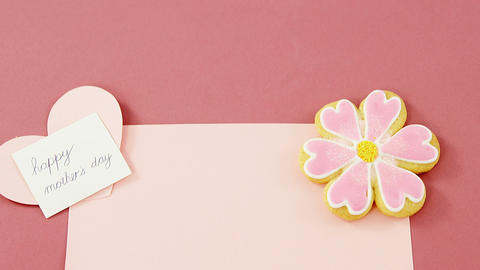 Flower shape cookie, heart shape card on red envelope against pink background Footage