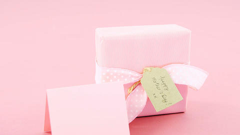 Gift box with happy mother day tag and blank card against pink background Live Action