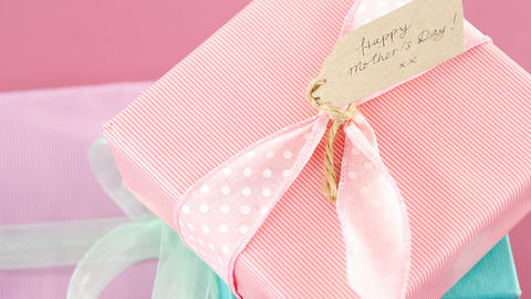 Gift boxes with happy mother day tag against pink background Live Action