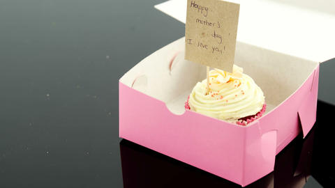 Cupcake with happy mother day card against black background Live Action