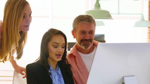 Male and female executives discussing over computer Live Action