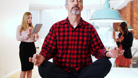 Male executive performing yoga while his executive standing in background Live Action