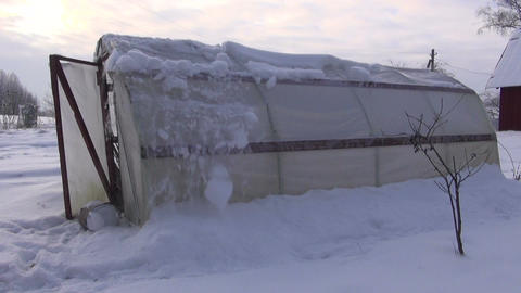 Gardener removing snow from polyethylene greenhouse Footage