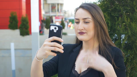 Closeup of young urban business woman taking selfie with smartphone in the city Footage