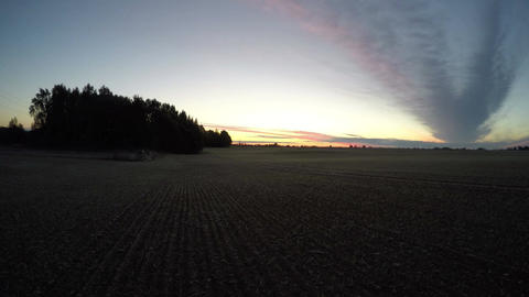 Sunrise over the field with clouds moving, time lapse 4K Footage