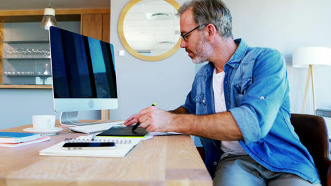 Male graphic designer using graphic tablet at desk Live-Action
