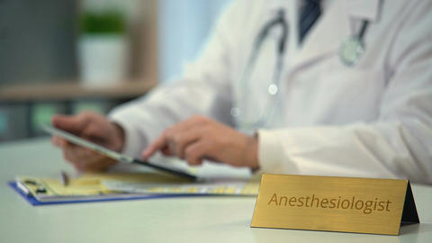 Anesthesiologist working on tablet PC in clinic, conducting medical research Footage