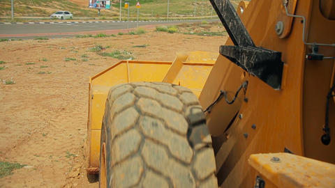 Tractor with a bulldozer moving soil at a construction site - View from the trac Filmmaterial