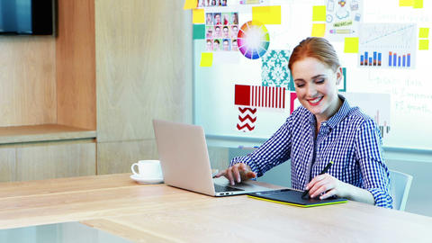 Female graphic designer using laptop and graphic tablet in conference room Live Action