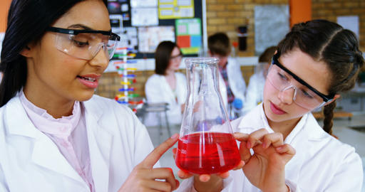School girls experimenting with chemical in laboratory at school Footage