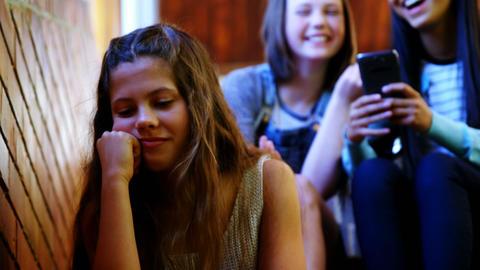 School friends bullying a sad girl in school corridor Live Action