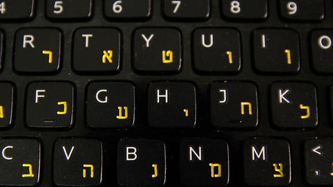 Man typing on a keyboard with letters in Hebrew and English Footage