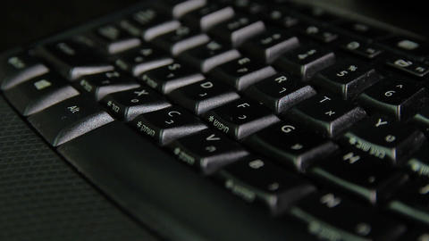 Man typing on a keyboard with letters in Hebrew and English - Wireless keyboard