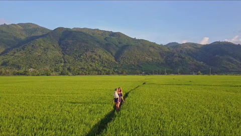 Woman Carrying Girl Approaches Drone Camera among Fields Footage
