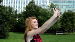 young attractive woman is in park - woman photographs herself (selfie) - nature  Footage