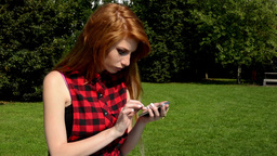 Young attractive woman is in the park and smiles - woman works on the smartphone Footage