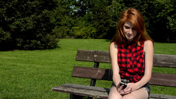 Young attractive woman sits on bech in the park and listens music on smartphone  Footage