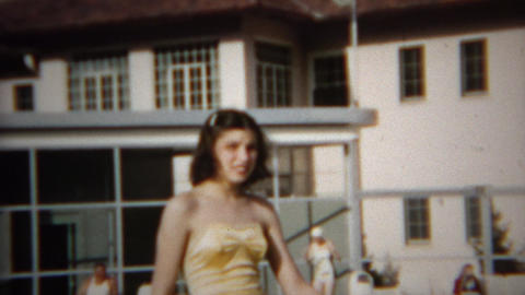 1952: Teenage girl old timey bathing suit seated at country club pool Footage