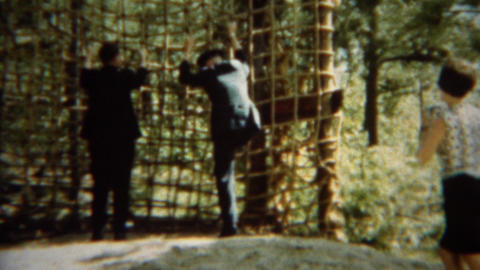 1966: Formal military uniformed cadet climbing up rope cargo net Live Action