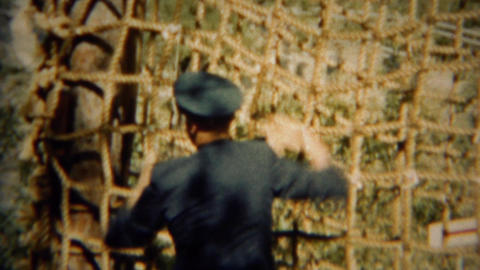 1966: Formal military uniformed cadet climbing down rope cargo net Live Action