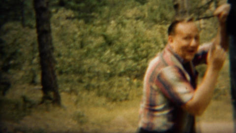 1966: Middle aged man monkey bar fail as military son laughs Footage