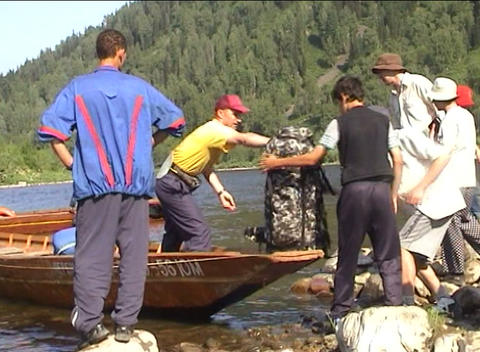 Tourists unload backpacks from boat after crossing Footage