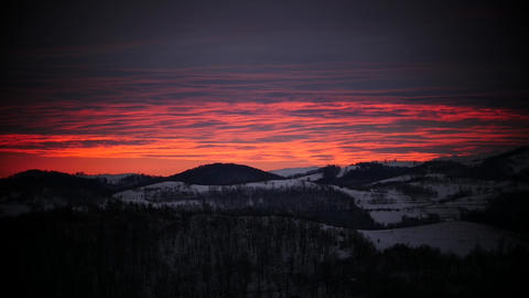 Reddish Sunrise Over Some Mountains With Snowy Forests 694 stock footage