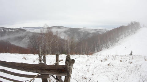 View over the mountains which are loaded with snow with wisps of fog that climb  Footage