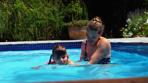 Mother assisting daughter in swimming Footage