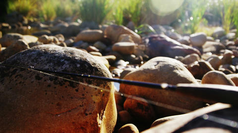 Fly fishing rod, reel and hook on rock Footage