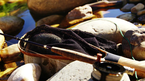 Fly fishing rod, reel and tackle box on rock Footage