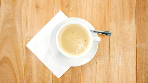 Overhead view of white coffee cup with creamy froth Live Action