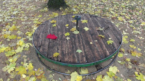 Yellow maple leaves and red glove spinning on children playground equipment Footage