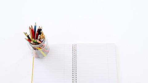 Colored pencils kept in pencils holder kept on blank paper Footage