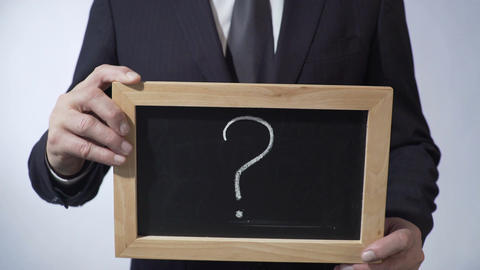 Question mark written on blackboard, business person holding a sign in hands Footage