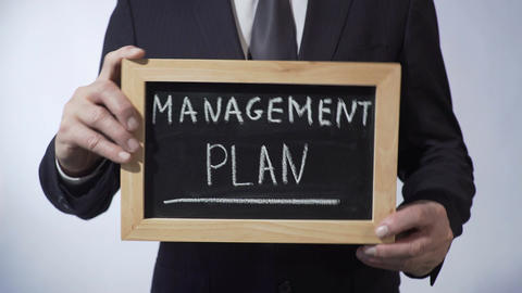 Management plan written on blackboard, business person holding sign, strategy Footage