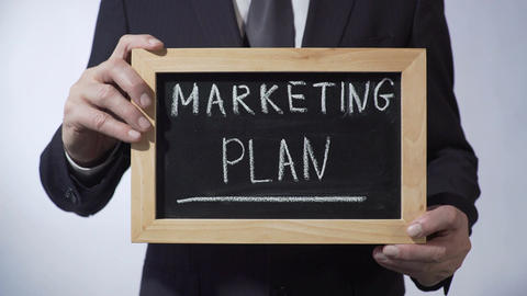 Marketing plan written on blackboard, man in black suit holding sign, business Footage