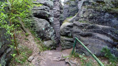 Walk in narrow path in corridor between great sand rocks Filmmaterial