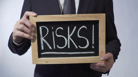 Risks with exclamation mark written on blackboard, business person holding sign Footage