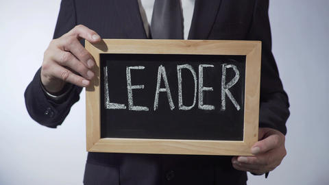 Leader written on blackboard, businessperson holding sign, business concept Footage