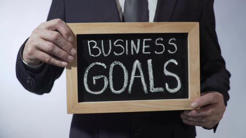 Business goals written on blackboard, businessman holding sign, strategy Footage